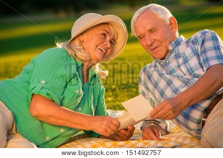Senior couple looking at photograph. Smiling woman looks at man. Lots of good memories. Time is running so fast.