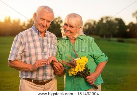 Senior couple with bouquet smiling. Man holding hand of woman. Life is meant for love. Feelings grow stronger with time.