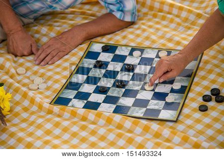 Hands of seniors playing checkers. Checkered yellow cloth. Game for smart people. Attention and logic.