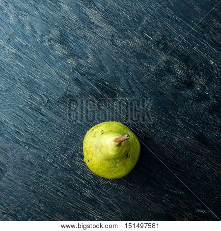 Green pear on a dark background