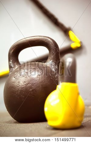 Colorful kettlebells weights on gym floor - focus on the dark kettle bell