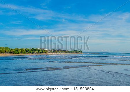 Beautiful seascape of ocean with a stretch land extending out into the water and a blue sky with wispy clouds in the background.