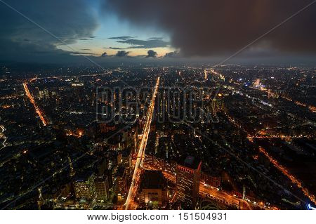 Moody aerial night view of city lights across Taipei, Taiwan just after sunset