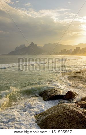 Sunset at Arpoador beach in Ipanema in Rio de Janeiro with the hill Two Brother and stone Gavea in the background