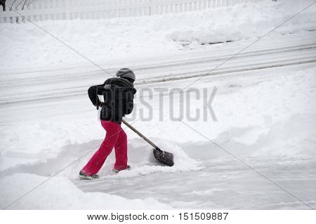 women removing snow on the driveway by shovel after blizzard