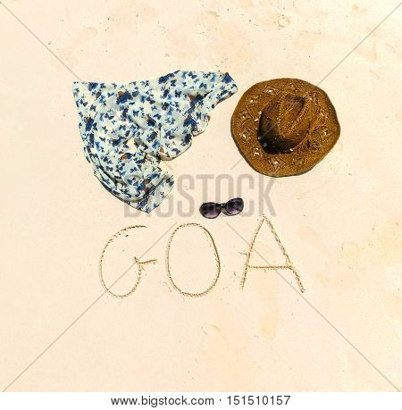 The straw hat mask sun glasses and dress on a tropical beach and inscription on sand Goa .