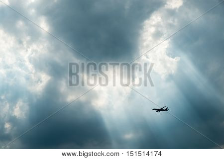 Passenger airplane in the clouds and sun-ray.