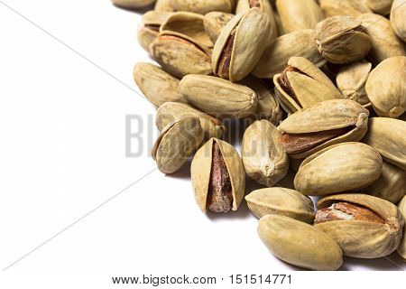 Pile of brown roasted pistachios isolated on white background. Snack. Isolated pistachios