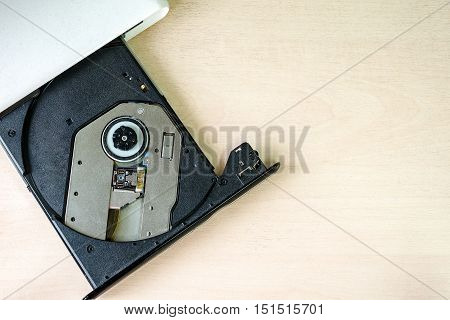 Portable CD/DVD drive on wooden background. Slim external