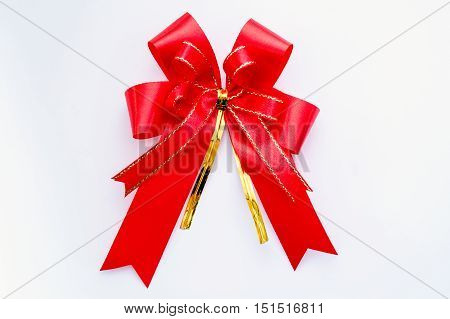 Red and gold satin ribbon on white background.