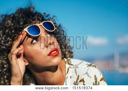 Portrait of adorable mixed race girl raises sunglasses and looking up at sky