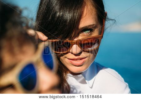 Portrait of pretty brunette girl looking at camera over sunglasses. Another woman in foreground.