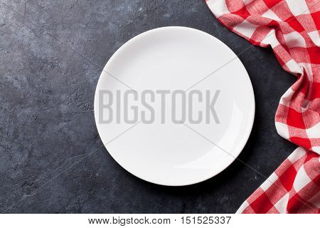 Empty plate and kitchen towel over stone table. Top view with copy space for your recipe