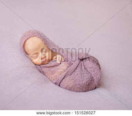 lovely sleeping newborn baby swaddled in pink diaper