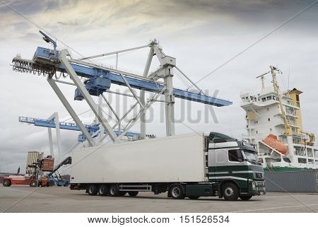 Truck, Lorry Waiting In Port For Cargo By Crane