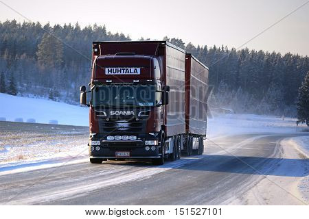 SALO FINLAND - JANUARY 16 2016: New dark red Scania cargo truck on icy road on a winter afternoon in South of Finland.