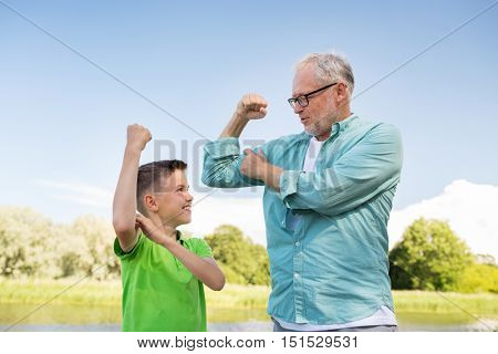 family, generation, power and people concept - happy grandfather and grandson showing muscles