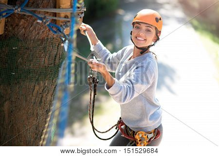 Need to be careful. Attractive emotional well built woman wearing a special outfit and holding on to the ropes while being in the adventure park