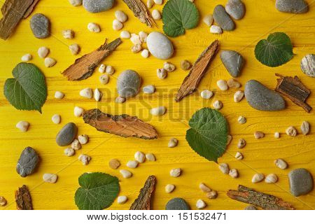 Scattering of pebbles, leaves and pieces of bark on yellow wooden background