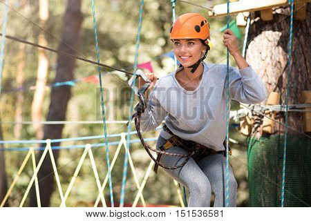 On the way to adventures. Pleasant determined cheerful woman holding the ropes and preparing to start moving forwards while having fun in the rope park