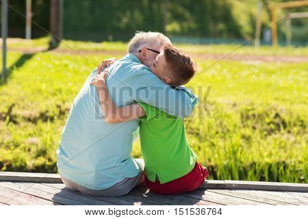 family, generation, communication and people concept - happy grandfather and grandson hugging on berth