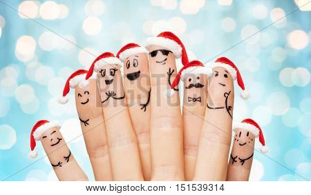 family, holidays, christmas and body parts concept - close up of fingers with smiley faces and santa hats over blue lights background