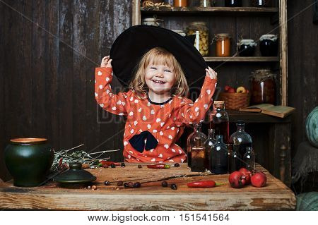 Little girl witch in black pointed hat over wooden table and magical accessories. Halloween, the studio evening.
