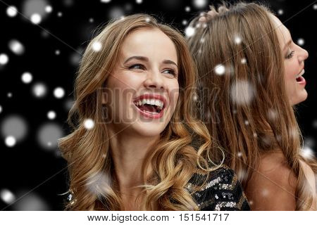 new year party, christmas, winter holidays and people concept - happy young women dancing at night club disco over black background with snow
