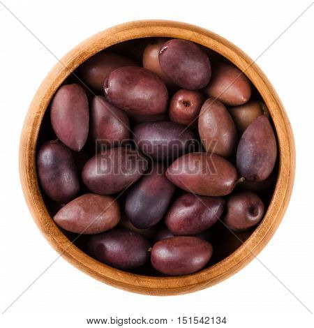 Kalamata black olives in a wooden bowl over white. Greek large purple table olives. A variety grown elsewhere are called Kalamon olives. Dried ripe fruits of Olea europaea. Macro close up food photo.