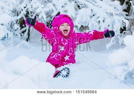 happy little girl playing in the snow sitting