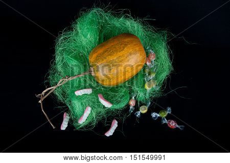 Orange pumpkin in green synthetic grass with round sweets and candies in shape of teeth laying on black background