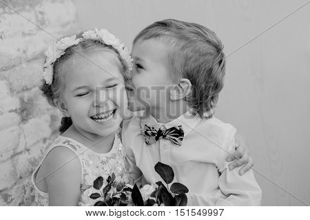 Happy little children embrace and kiss on a light background ( black and white )