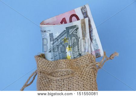Euro currency in a brown hessian bag.
