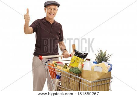 Cheerful senior posing with a shopping cart full of groceries and giving a thumb up isolated on white background