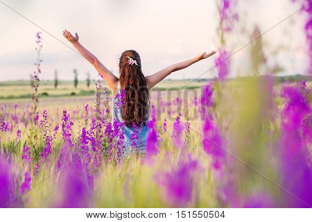 girl stands in a field of wildflowers hands up