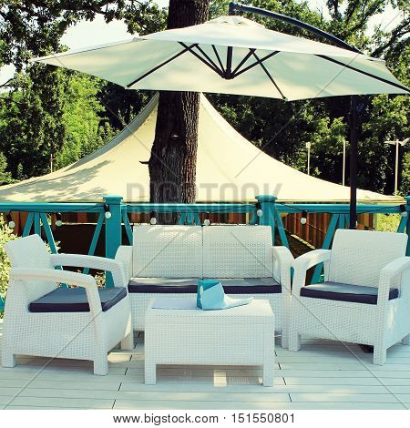 Al fresco cafe with white rattan wicker armchairs and tables on the summer garden terrace. Square toned image
