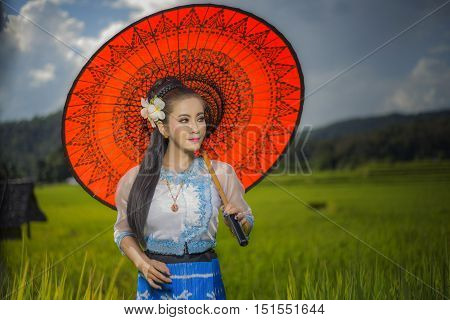 Beautiful Asian Girl In Myanmar Traditional Costume, With Red Bamboo Umbrella On On Rice Fields Sky
