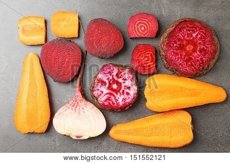 Fresh young sliced beets and carrots on grey background