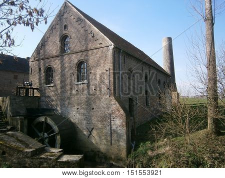 photo of an acient builing with a watermill