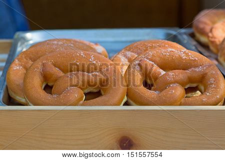 Closeup tray of fresh soft and sweet Pretzel dusted with sugar