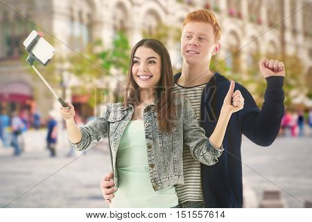 Young happy couple taking selfie on blurred city street background.