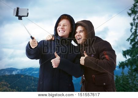 Young happy men taking selfie on blurred nature background.