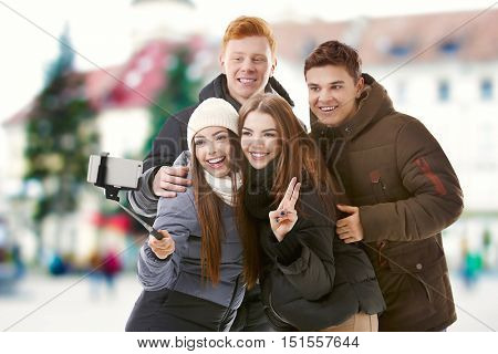 Group of young people taking selfie on blurred city street background.