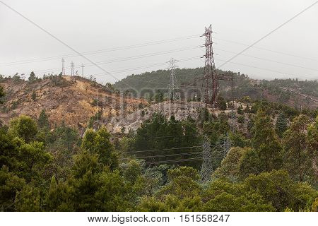 Electrical Transmission Towers criss crossing the hills near the west coast mining town of Queenstown Tasmania in early morning mist