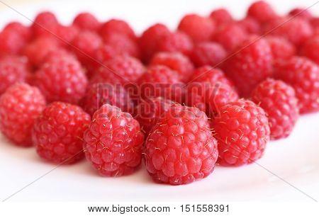 Fresh raspberries in heart shape on bright background