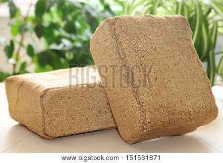 Alternative fuel, eco fuel, bio fuel. Wood sawdust briquettes for stoves. Lean-burn with good heat output. Briquettes from sawdust on a green background.