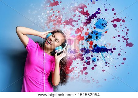 Young woman listening to music in headphones. Colorful design on blue background.