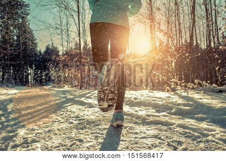 Woman Running at snowly winter under sunlight.