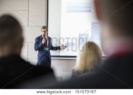 Businessman giving presentation in seminar hall at convention center
