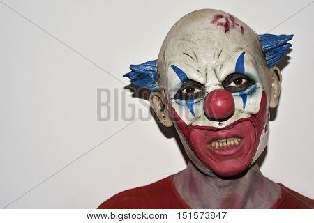 closeup of a scary evil clown against an off-white background